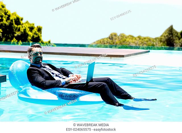 Businessman using laptop on inflatable