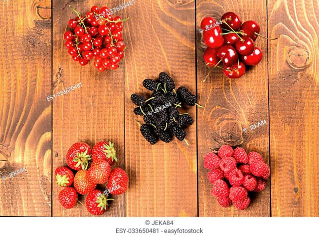 Collection of cherries, strawberries, mulberries, red currants, raspberries on wood background