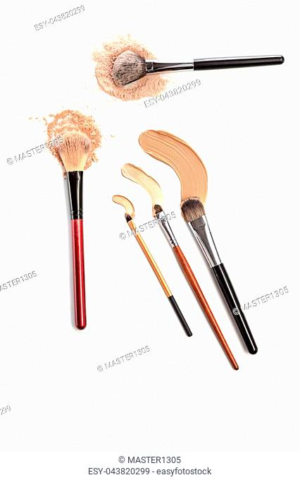 Close-up of crushed mineral shimmer powder golden color with makeup brush on white background with Cosmetic foundation cream
