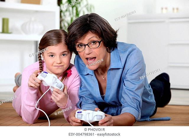 Grandmother playing a video game with her granddaughter