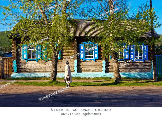 A Russian woman walks in front of a traditional log house in the 'Old Believers' Village', settled by members of a 'heretical' offshoot of the Russian Orthodox...