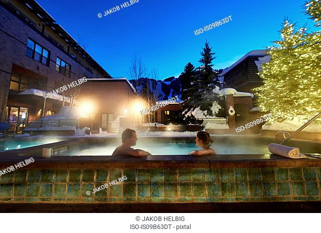 Mature couple relaxing in outdoor hotel hot tub at dusk, Aspen, Colorado, USA