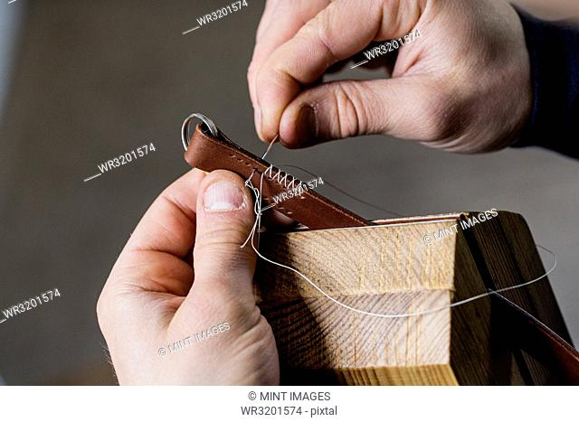 Close up of craftsman making brown leather camera strap, hand stitching two pieces of leather, held in a clamp