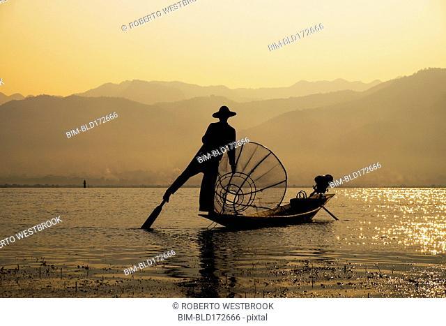 Asian fisherman rowing canoe on rural lake
