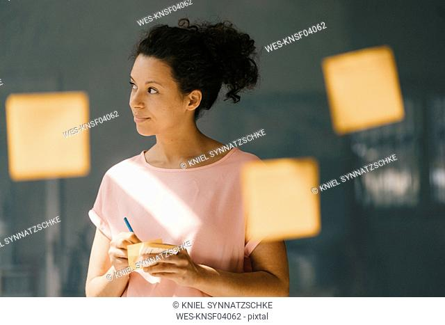 Woman brainstorming in office usine adhesive notes