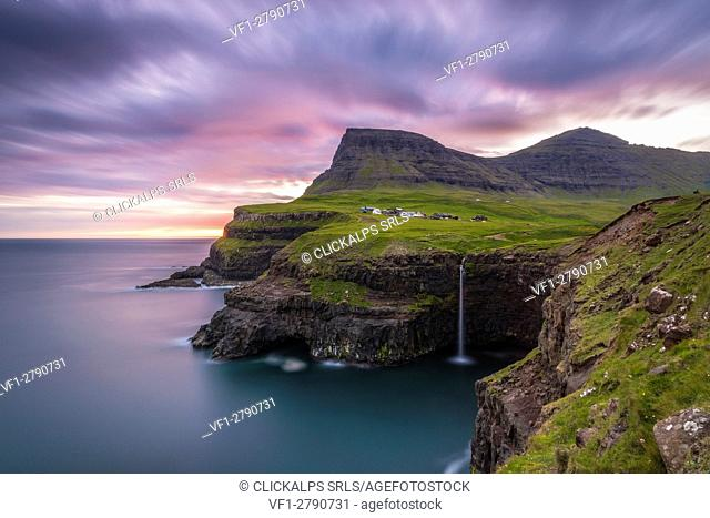 Gasadalur, Vagar island, Faroe Islands, Denmark. The iconic waterfall jumping from the cliff into the ocean at sunset