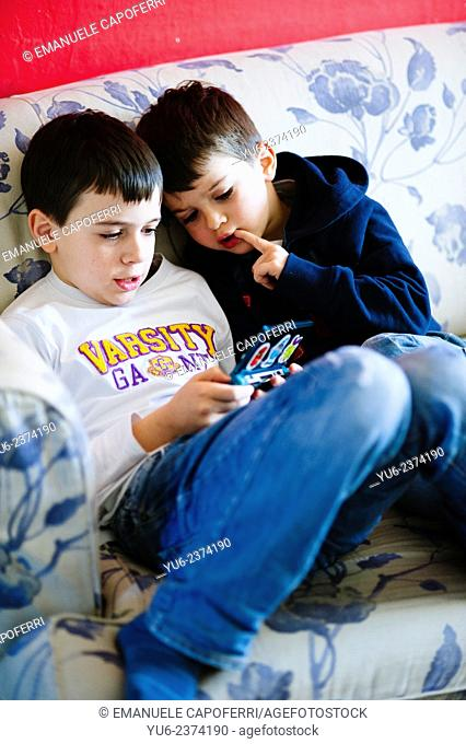 Brothers playing with portable video game
