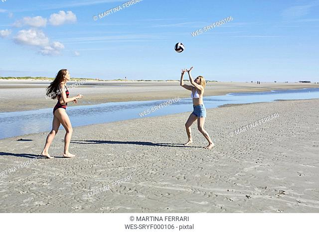 Two young women on the beach playing beach volleyball
