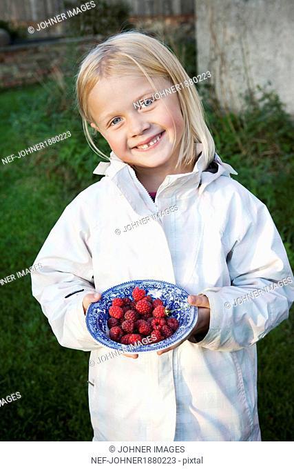 Smiling girl holding bowl full of raspberries