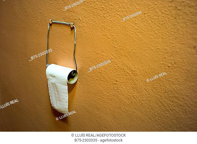 Loo roll hanging with a wire on the wall of an old WC