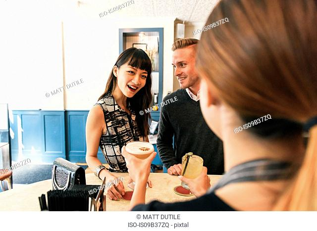 Young couple in bar, bring served drinks by bar worker