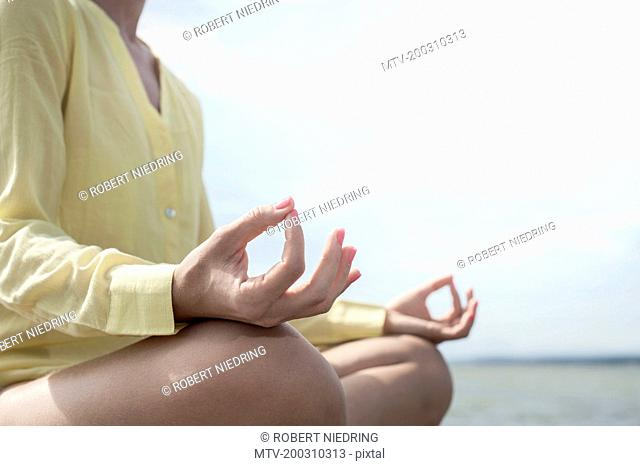 Mid section of a woman doing lotus pose yoga at the lake, Ammersee, Upper Bavaria, Germany