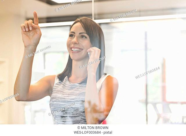 Young businesswoman on the phone with index finger on wndow pane
