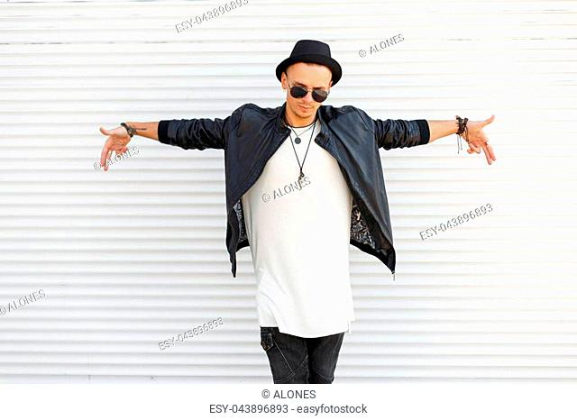 Handsome young man with a fashionable hat wears sunglasses in a trendy, stylish clothes near white metal wall