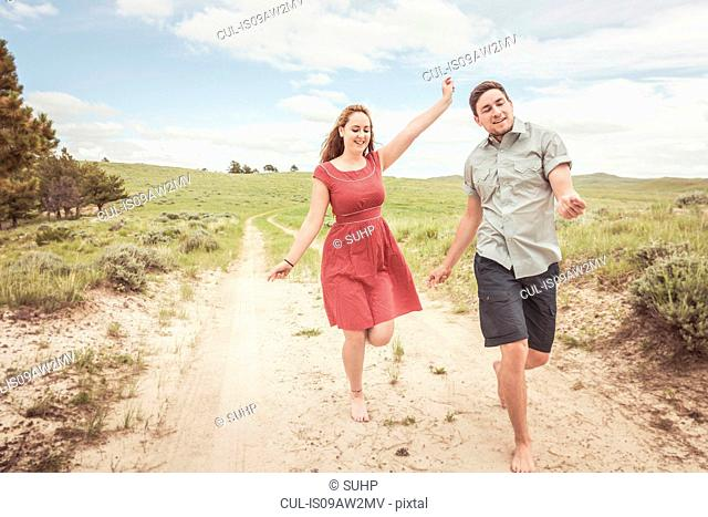 Happy young couple running barefoot along sandy track, Cody, Wyoming, USA