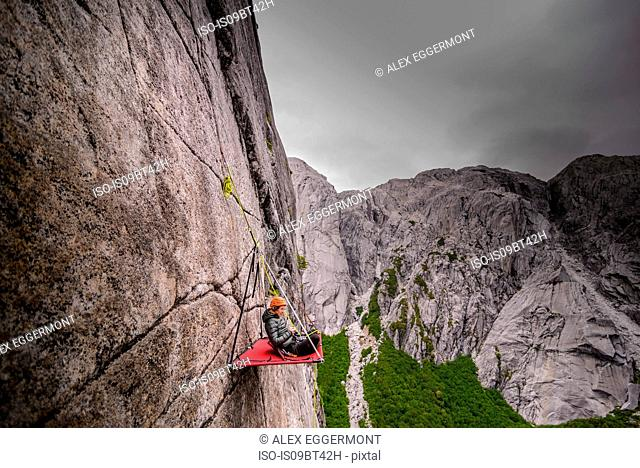 Woman sitting on portaledge, Cochamo, Los Lagos, Chile