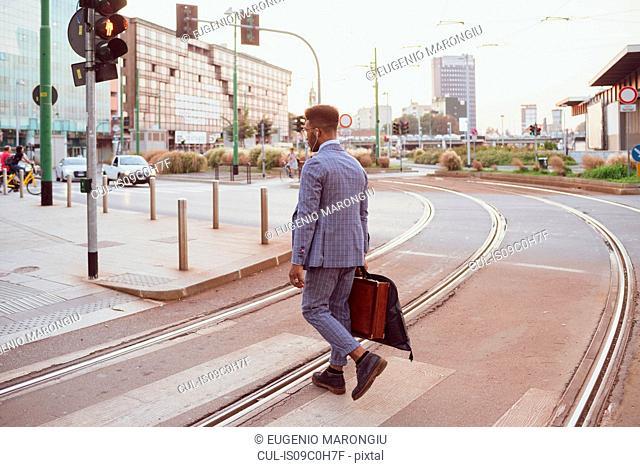Businessman crossing tram line, Milano, Lombardia, Italy