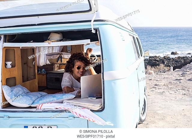 Spain, Tenerife, smiling woman looking at laptop in van