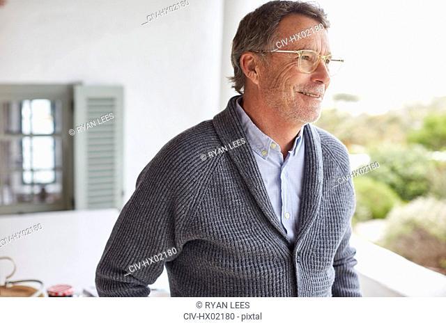Smiling senior man looking away on patio