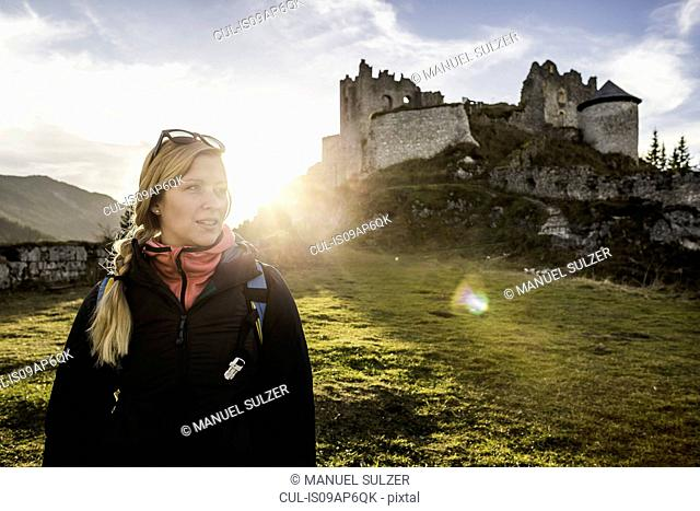Young female hiker in front of Ehrenberg castle ruins, Reutte, Tyrol, Austria