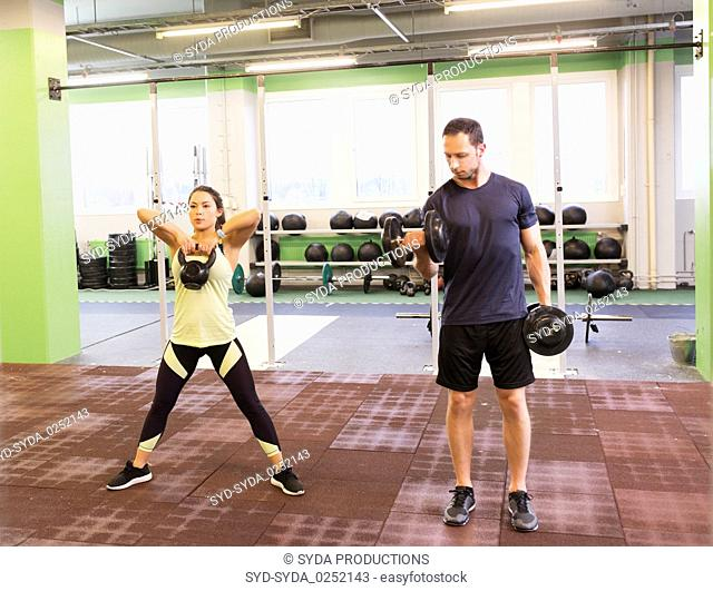 man and woman with kettlebell exercising in gym