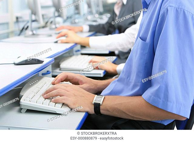 Human hands typing on the keyboard in the computer room