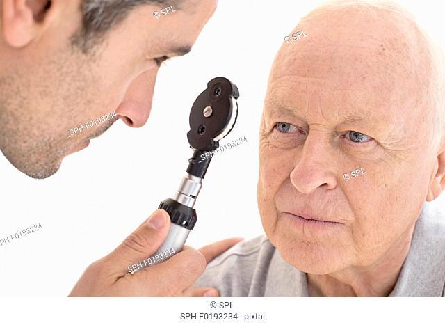 Male doctor examining senior patient's eye