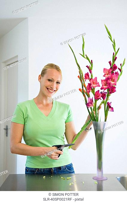 Smiling woman arranging flowers in vase