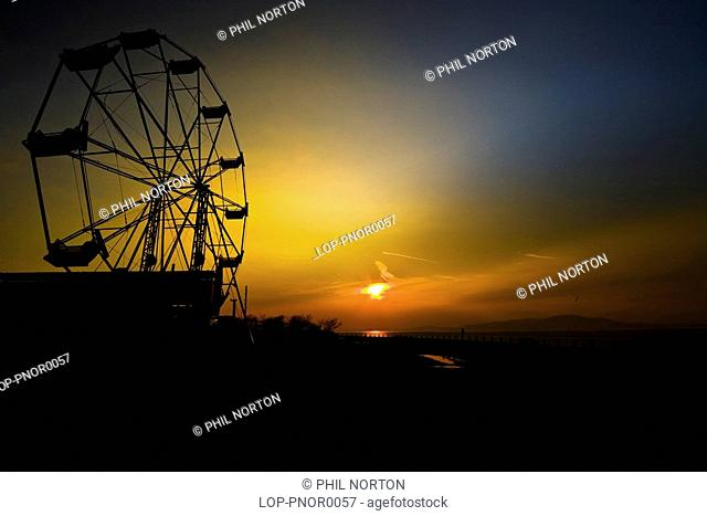 England, Cumbria, Silloth, A silhouette of a ferris wheel at sunset in Silloth