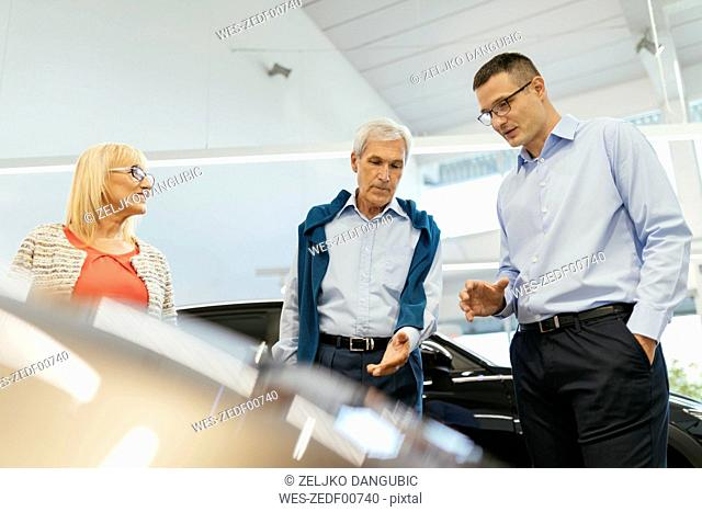Senior couple couple talking with salesperson in car dealership