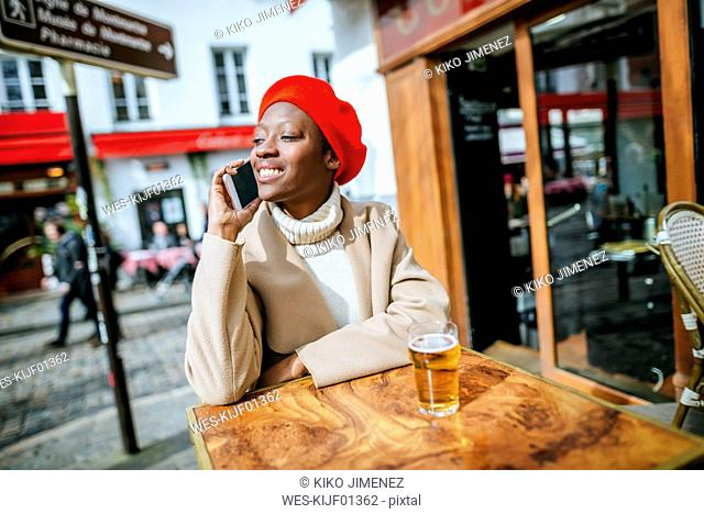 Young woman in Paris sitting in cafe and talking on the phone
