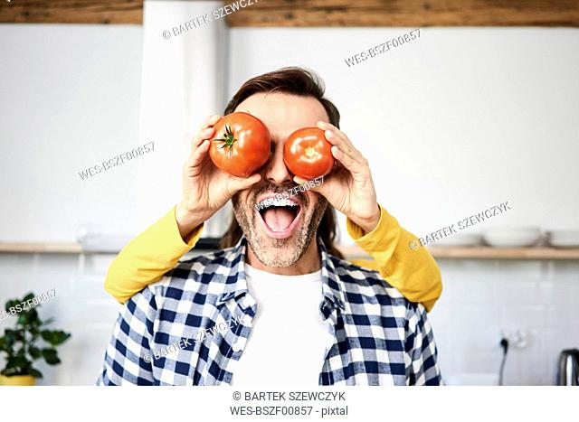 Couple having fun in the kitchen, playing with tomatoes