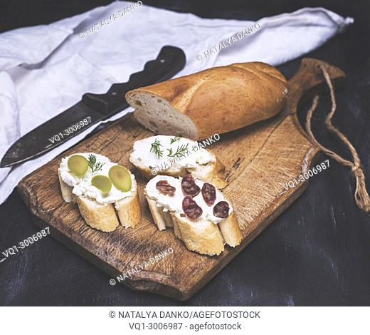 three sandwiches with cream cheese on a brown wooden board, toning