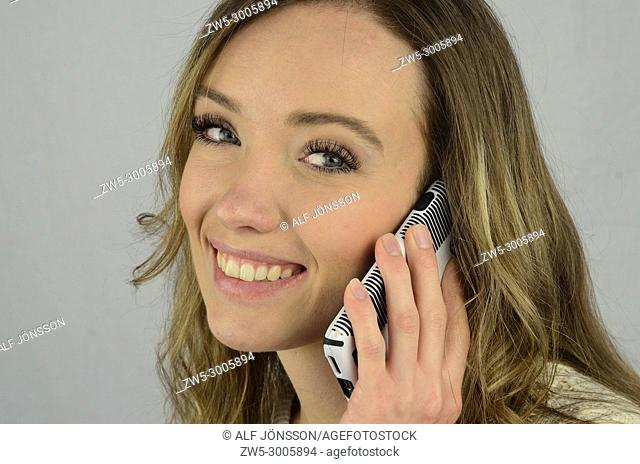 Portrait on an young smiling woman who talking in a mobil phone