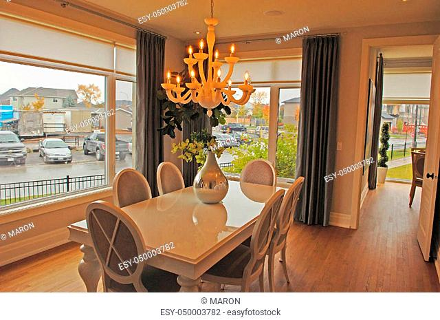 A gorges dining room in a new house with a chandelier, large windowsand a table with 6 chairs
