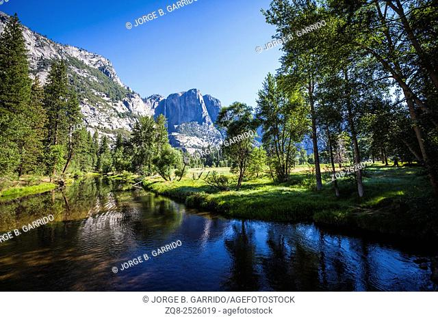 Merced river in Yosemite valley with mountains and waterfall on background, Yosemite National Park, California