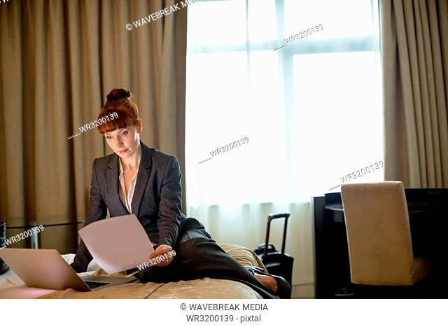 Businesswoman looking at documents on a bed
