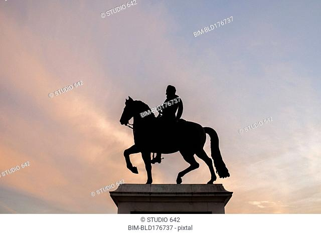 Silhouette of horse and rider statue under sunset sky