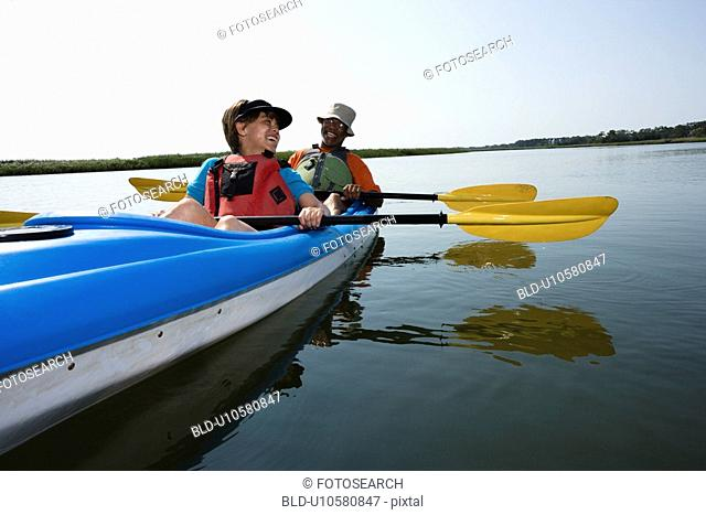 African American middle-aged couple sitting in kayak on lake smiling and laughing