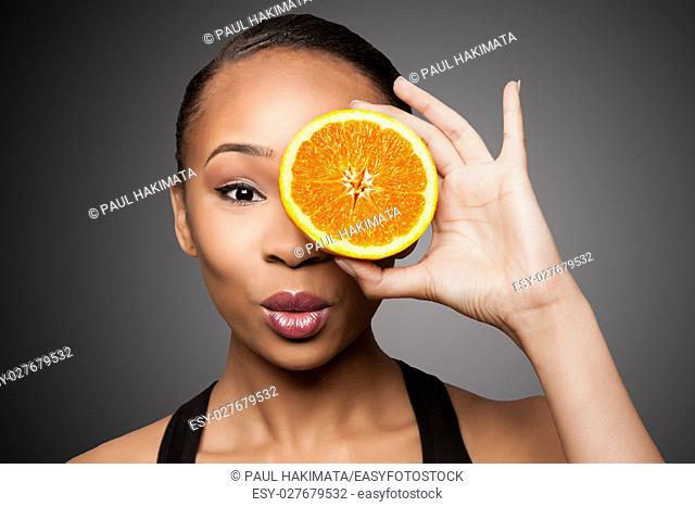 Beautiful healthy happy black asian woman holding delicious orange mandarin fruit in front of eye