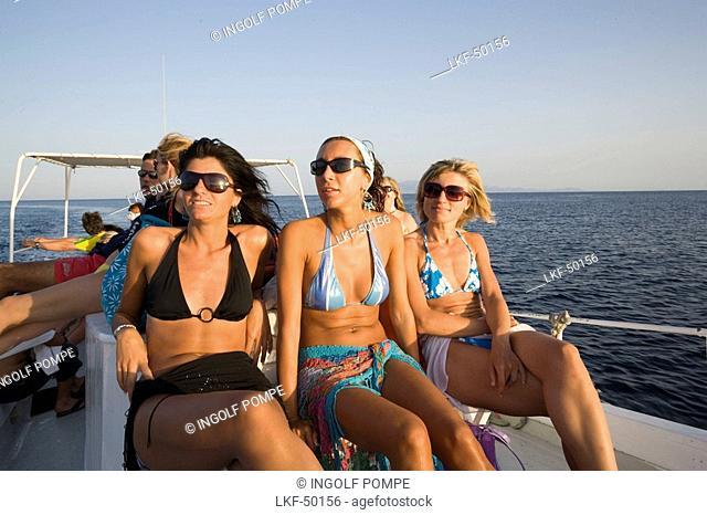 Three women using the boat transport to the Paradise and Super Paradise Beach, Psarou, Mykonos, Greece