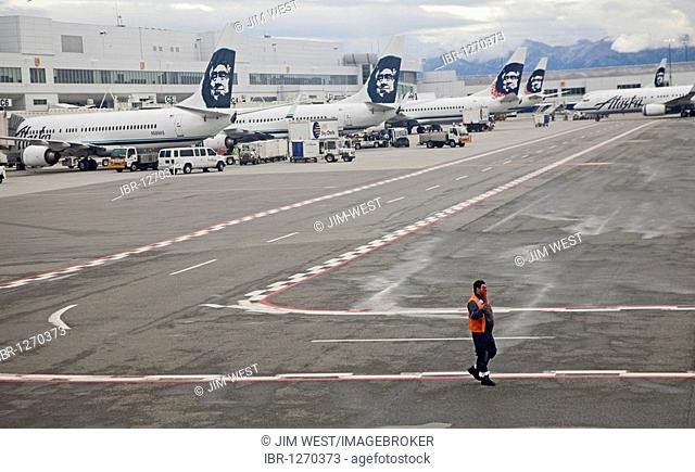 A worker guides an aircraft leaving the Anchorage Airport, Anchorage, Alaska, USA