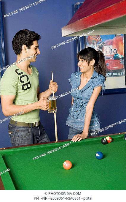 Young couple toasting beer glasses in the pool room