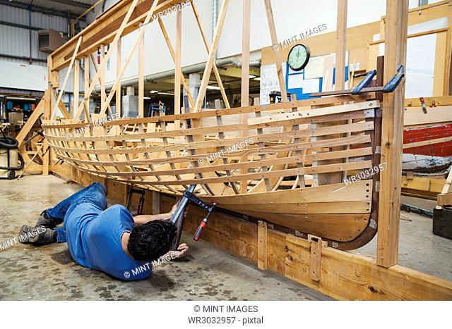 Man lying on floor in a boat-builder's workshop, working on a wooden boat hull