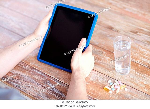 medicine, technology, nutritional supplements and people concept - close up of male hands with tablet pc computer, pills and water on table