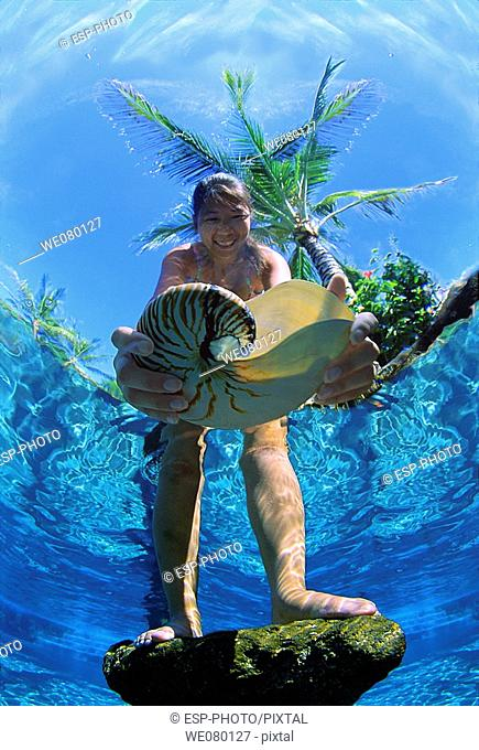Women picking up Underwater Seashell