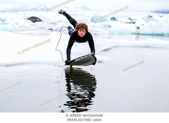 Caucasian surfer leaping on board in glacial water