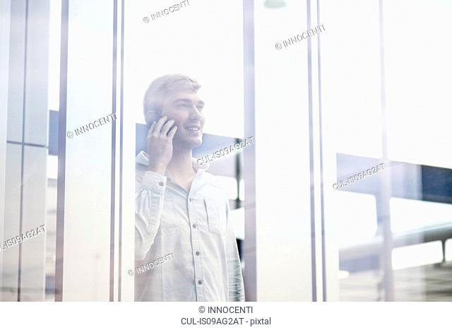 Young man behind reflective glass talking on smartphone
