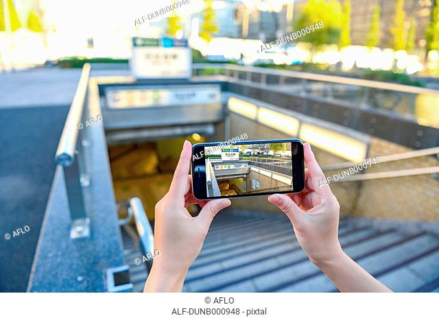 Japanese woman using augumented reality app on smartphone downtown Tokyo, Japan