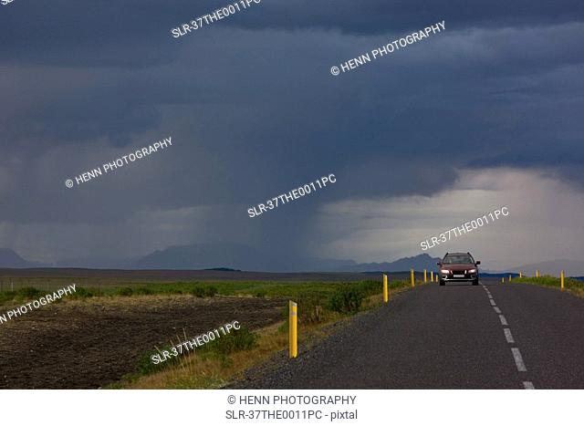 Car on rural road under dramatic sky